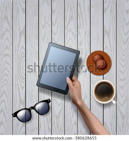 Vector hands holding empty black tablet computer with cup of black coffee and sunglasses, chocolate candy. coffee break. workspace on white wooden vector background - stock vector