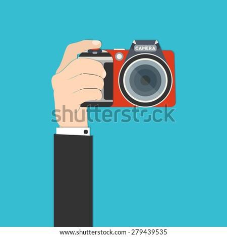 Vector illustration of a hand holding digital SLR camera for your design - stock vector