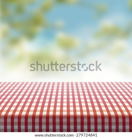 Vector picnic table covered with tablecloth on blurred background. - stock vector