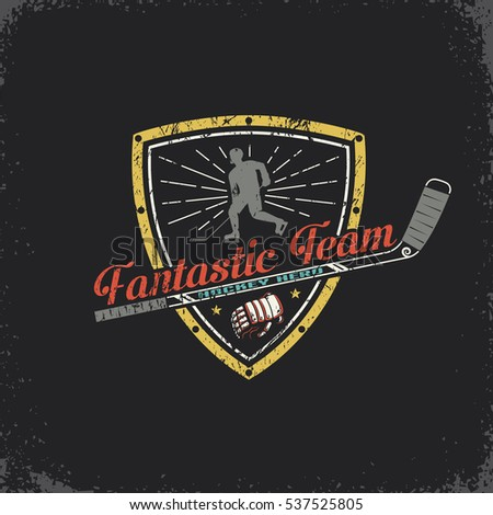 Vintage Hockey emblem with shield, player, stick and an inscription. Vector layered illustration.