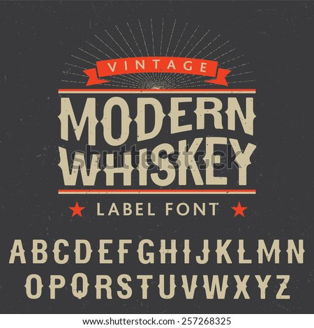 Whiskey label font and sample label design with decoration and ribbon. Vintage font. Whiskey font. Fine label font. Handcrafted font. Decoration font. Font style. Retro font. Old font. Stylized font. - stock vector
