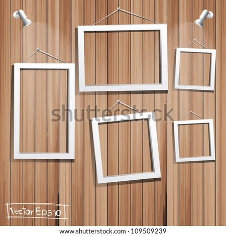 White frames on wood wall - stock vector