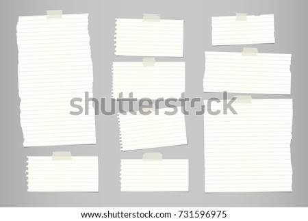 White ripped striped note, notebook paper for message or text stuck with sticky tape on gray background.