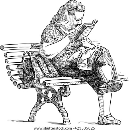 woman reads on a park bench
